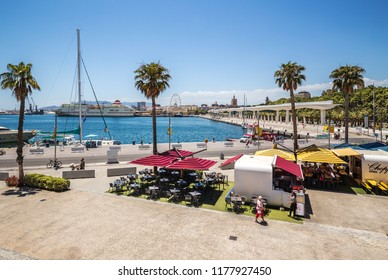 Malaga, Spain - June 20, 2018: Promenade of Malaga with a view of the pedestrian area, the port, the Ferris wheel and cafe.