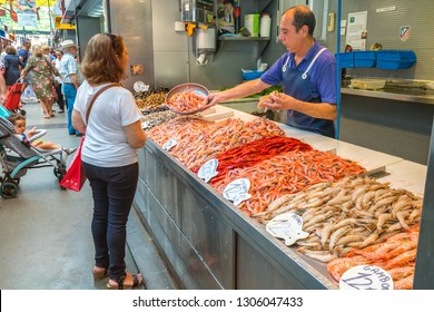 Malaga, Spain - June 26, 2018: Seller shows fresh shrimp to buyer in the popular central market in Malaga, Spain.