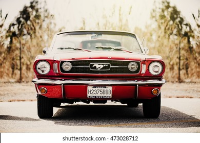 MALAGA SPAIN - JUNE 30, 2016. A classic Ford Mustang convertible in red color parked out of the city. Ford mustang is one of the most famous cars in the USA, and is an icon of muscle cars in the world