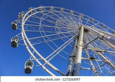 MALAGA, SPAIN - JUNE 6, 2018: A big Malaga Ferris wheel (La Noria de Malaga). Ferris wheel situated on a waterfront of the port of Malaga.