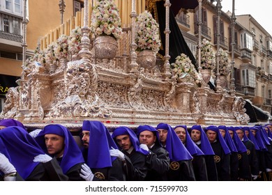 MALAGA, SPAIN - March 21, 2016: Semana Santa-procession of the Brotherhoof of Crucifixión on holy Monday in rainy wheather. Nazarenos, or penitents, line the Calle Carretería in the procession.