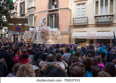 Malaga, Spain - March 21, 2016: procession of Gitanos brotherhood passing Plaza del Teatro. Rainy wheather but streets are packed with spectators looking at a float with a statue of Jezus Christ.