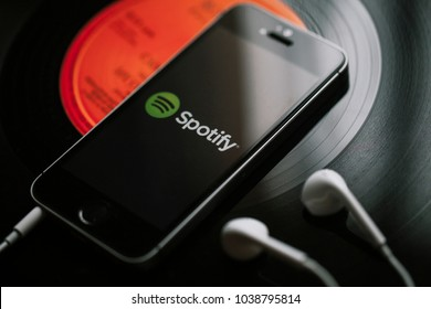 MALAGA, SPAIN - MARCH 5, 2018: Mobile phone with Spotify Music service in the screen and white earphones on a black vinyl record.