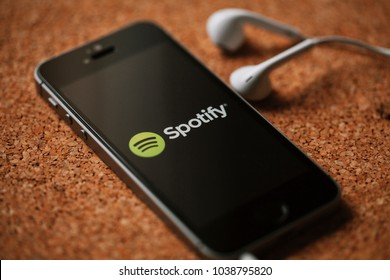 MALAGA, SPAIN - MARCH 5, 2018: Mobile phone with Spotify logo in the screen and white earphones, placed on a cork panel.