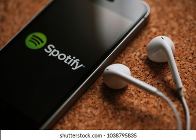 MALAGA, SPAIN - MARCH 5, 2018: Close up of mobile phone with Spotify logo in the screen and white earphones, placed on a cork panel.