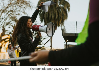 MALAGA, SPAIN - MARCH 8 th, 2020: Young woman shouting with a megaphone in the hand during feminist strike in Malaga, Spain, on March 8 th, 2020.