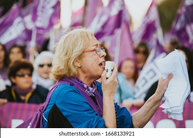Malaga, Spain - March 8th, 2020:  Old woman shouting with a megaphone in the hand during feminist strike in Malaga, Spain, on March 8 th, 2020.