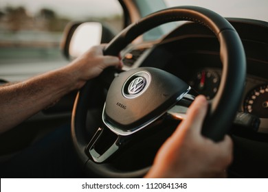 MALAGA, SPAIN - May 11, 2018: Man holding Volkswagen Transporter steering wheel while driving with a sunset light entering through the window on May 11th 2018.