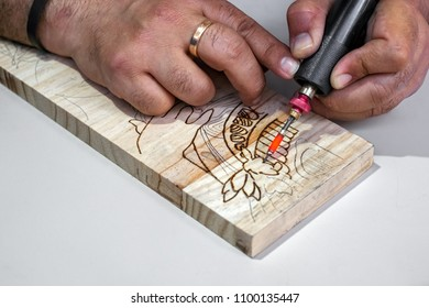 Malaga, Spain - May 25, 2018. A man engraving on wood. The pyrography.