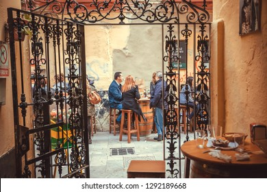 MALAGA, SPAIN - NOV 23: Group of relaxing people drinking at outdoor restaurant in traditional spanish style on November 23, 2018. Andalusian city with population of 600,000