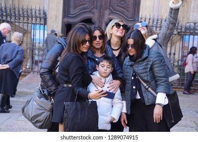 MALAGA, SPAIN - NOV 24, 2018 - Young boy taking selfie with his female relatives in front of the Cathedral of Malaga, Spain