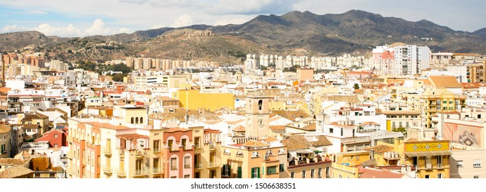 Malaga, Spain - October 20 2012 - A panoramic, aerial view of Malaga's skyline with mountains and a cloudy sky as a backdrop.  Image has copy space.