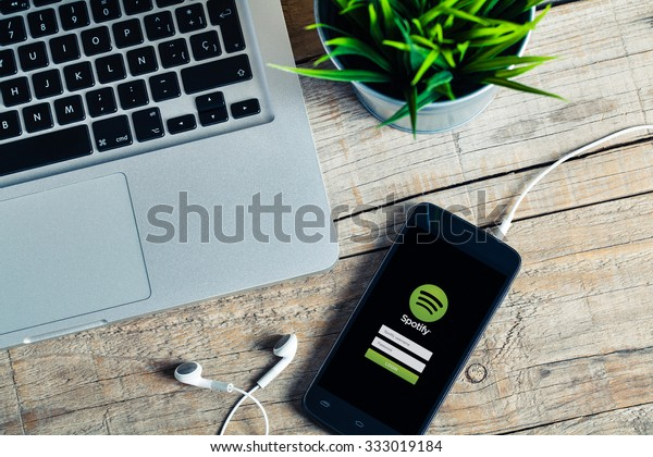 MALAGA, SPAIN - OCTOBER 29, 2015: Spotify app in a smart phone screen. Workplace with a laptop, an earphones and a plant, over a wood table. Spotify is the most famous app to listen and share music.