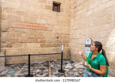 MALAGA, SPAIN - September 2nd, 2018: Tourist guide giving explanations at Picasso Museum entrance, located in an old classic palace in the city of Malaga, Spain.