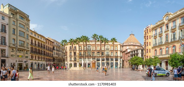 MALAGA, SPAIN - September 2nd, 2018: Panoramic cityscape of Constitution Square with visitors walking along it, during a journey in the city center of Malaga, Spain.