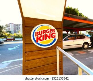 Malaga/Spain - 02-27-2019 : Burger King hamburger chain restaurants logo on a wooden background: Parking in the background.