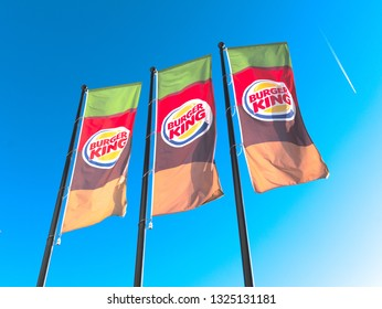 Malaga/Spain - 02-27-2019 : three flags waving with the colors (green, red, orange, brown) and the logo of the food restaurant company Burger king (written on the flag). Nice blue sky sunny day,
