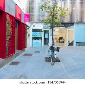 Malaga/Spain - 03-21-2019 : green bike against a small tree on a public place downtown with a trendy arty shop  with red doors on the left.