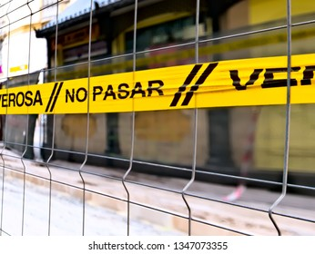Malaga/Spain - 03-22-2019 : Yellow tape tied on a grill saying in Spanish ¨no trespassing¨.