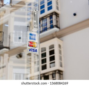 Malaga/Spain - 04-12-2019 : Three stickers of visa, MasterCard and american express stuck on an opened glass door of a restaurant. Nice old European buildings in the background.