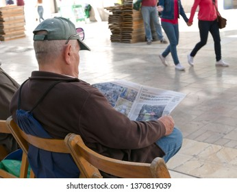 Malaga/Spain - 04-15-2019 : Caucasian old man seated on a public bench on a pedestrian busy street is reading the newspaper. People passing by.