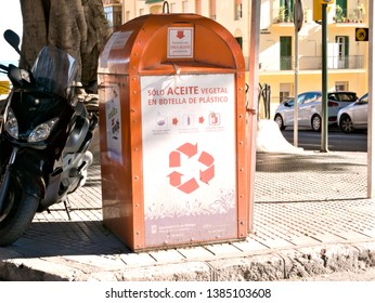 "Malaga/Spain - 04-28-2019 : Orange used oil collector on the street with inscriptions in Spanish ""only vegetable oil in plastic bottle"""