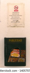 Malaga/Spain - 05-22-2019 : sign in Spanish saying no junk mail in the building, the company advertising will be held responsible. Small plastic container below with ads written in Spanish.