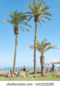 Malaga/Spain - 05-23-2019 : Nice sunny public beach in Malaga Spain. Grass and palm trees in the foreground, sand and people sunbathing in the foreground.