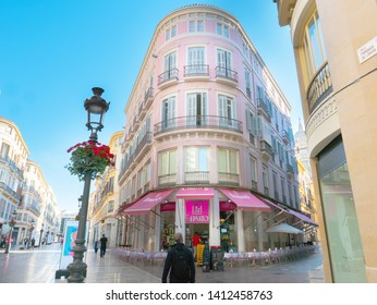 Malaga/Spain -05-27-2019 : Large pedestrian street in the Spanish town of Malaga with the facade of a pastel color flat iron shaped building against blue sky.