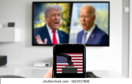 Malaga/Spain - 09-28-2020 : concept for usa presidential election 2020. Biden and Trump on TV in blurred background. Phone with photo of ballot box and usa flag.