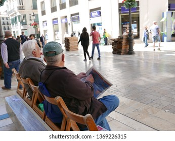 Malaga/Spain-04-12-2019 : Rear view of two old Caucasian men reading the newspaper, seated on a public bench on a pedestrian street. People walking passing by.