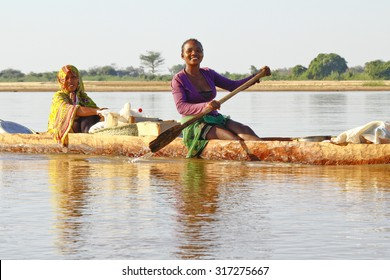 Malagasy people crossing the inlets in an outrigger canoe