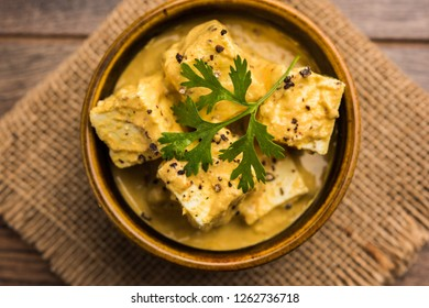 Malai or achari Paneer in a gravy made using Whipping Cream. served on a serving pan. selective focus