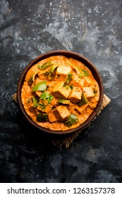 Malai or achari Paneer in a gravy made using red gravy and green capsicum. served in a bowl. selective focus