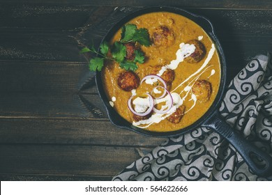 MALAI KOFTA CURRY with space for Copyscape Text on Left Malai Kofta is a Mughlai Speciality dish made with Deep fried Potato Paneer Balls simmered in Spiced Onion Tomato Gravy.