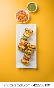 Malai Paneer Tikka Kabab - is an Indian dish made from chunks of cottage cheese marinated in spices, cream & grilled in a tandoor. Served in a plate with salad & green mint chutney. Selective focus