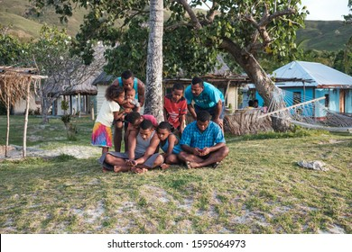 Malakati village, Fiji - 10/27/2019: Group of people watching rugby match on a small phone on the grass area close to the beach