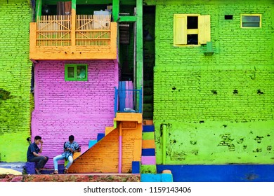 Malang, Indonesia - July 11, 2018: People walking in Jodipan village with colorful houses ( Kampung Warna Warni ). Popular place to visit for family holidays day tour. Travel destination in East Java.