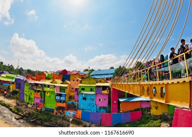 Malang, Indonesia - July 12, 2018: People walking by pedestrian bridge to old slum village Jodipan Kampung Warna Warni with colorful houses. Popular travel destination in East Java on family holidays