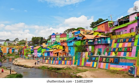 Malang, Indonesia - July 12, 2018: View of Jodipan village ( Kampung Warna Warni ) with entrance colorful signboard. Popular place to visit for city tour on holidays. Travel destination in East Java