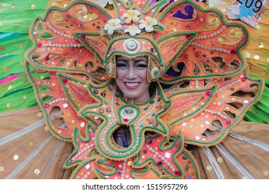 Malang, Indonesia - September 16, 2019: Unidentified woman displaying colorful costume during Malang Flower Carnival. The carnival is an anual event in this town. Beautiful Smile. MFC 2019