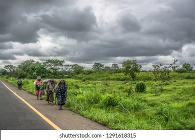 Malange / Angola - 12 08 2018 :Trip through Angola's lands 2018: View of elderly women farmers, walking on the side of the road, typical tropical landscape as background