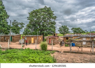 Malange / Angola - 12 08 2018: Typical village view, traditional terracotta houses with zinc plate cover and bricks, people and tropical landscape, in Angola