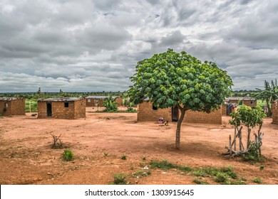 Malange / Angola - 12 08 2018: View of traditional village, people and thatched and zinc sheet on roof houses and terracotta brick walls, cloudy sky as background, in Angola