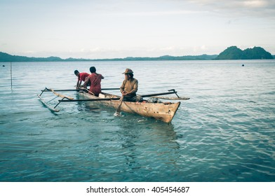 Malange, Indonesia - June 2015: Native men sit in canoe on sail on river in Malange, near coast of Togean islands, Sulawesi, Indonesia. Documentary editorial.