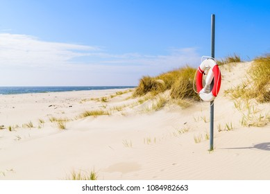 Malarhusen, Sweden - Lifebuoy on an empty sandy beach on a sunny day.