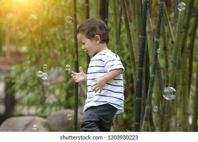 malay boy child playing soap bubbles outdoors