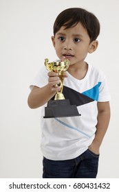 malay boy holding a trophy