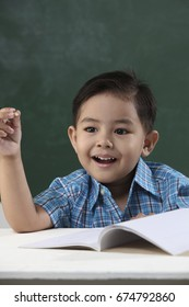 malay boy sitting in the classroom holding pencil