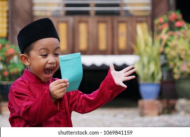 A Malay boy in Malay traditional cloth showing his happy reaction after received money pocket during Eid Fitri or Hari Raya celebration.